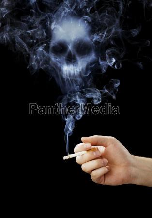 dlon trzymajaca papierosa smiertelnego dymu